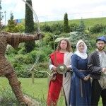 Three medieval characters next to statue of Robin Hood in Nottingham